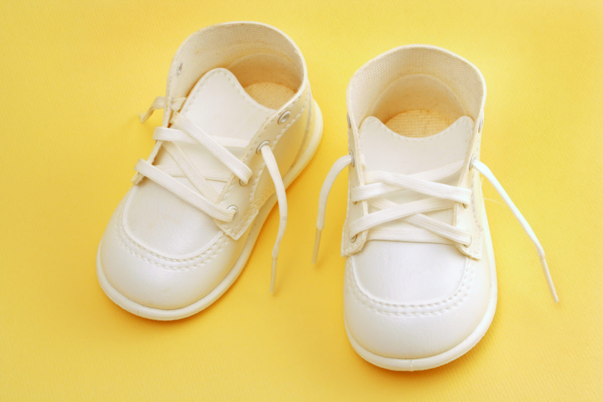 cute white child's shoes isolated over yellow