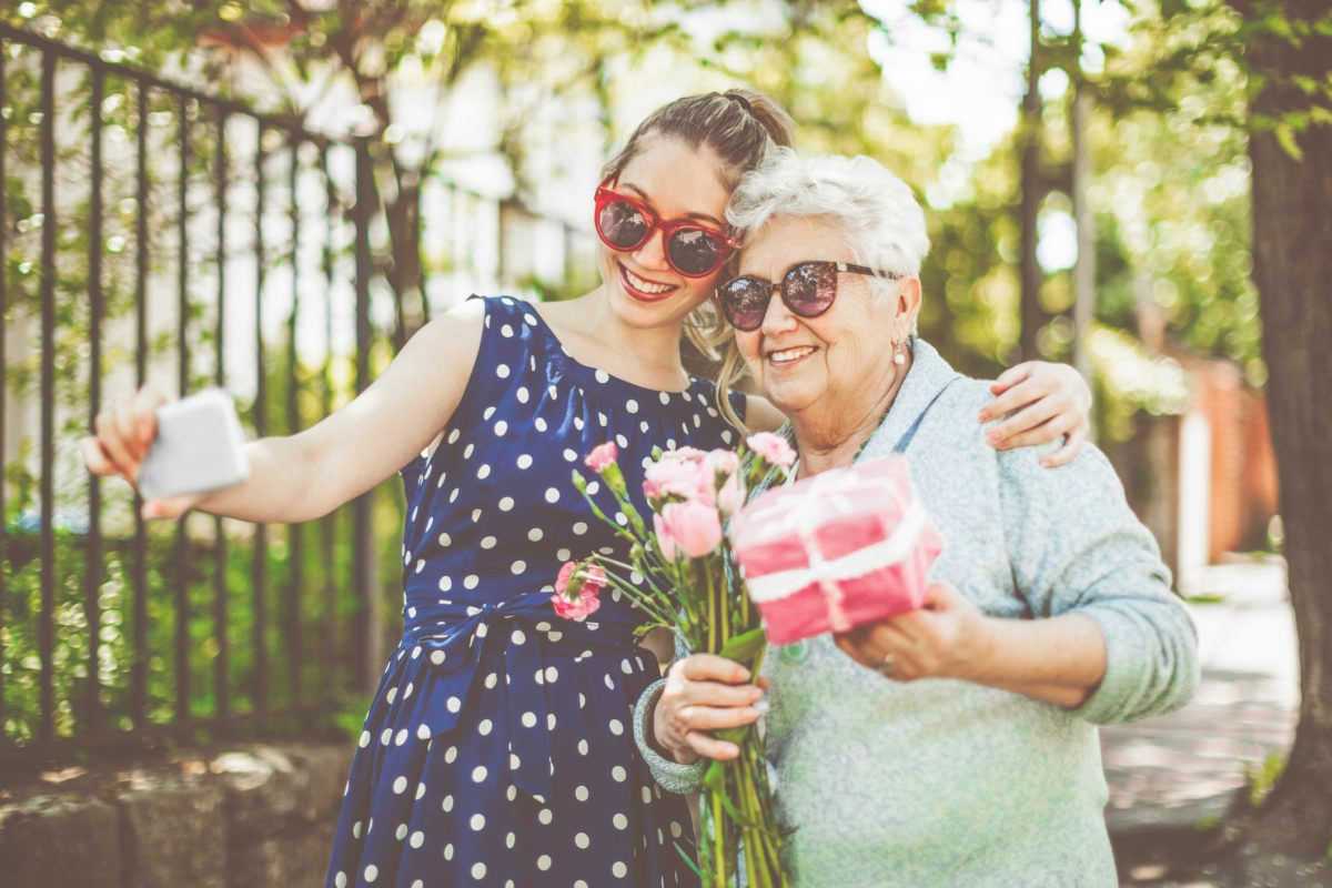 Smiling young teenager girl is taking selfies about herself and her grandmother while the beautiful senior woman is holding a gift and a bunch of flowers.