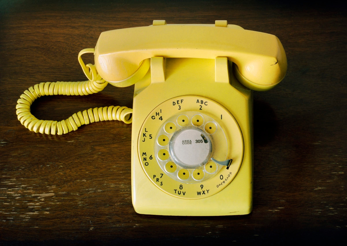 """This is a horizontal photograph of a bright yellow rotary phone. The perspective is overhead, looking down. The vintage telephone sits on top of a wood surface."""