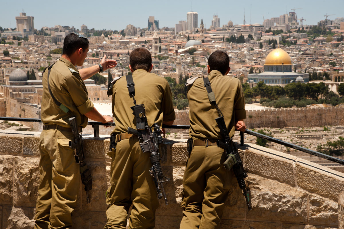 """""""East Jerusalem, Occupied Palestinian Territories - June 2, 2012: Israeli soldiers armed with assault rilfes look out over the Old City of Jerusalem and the Dome of the Rock from a lookout point on the Mount of Olives. Annexed by Israel in 1967, East Jerusalem, including the Old City, are still considered occupied Palestinian territory under international law."""""""