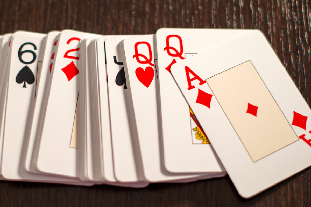 Deck of playing card spread out on a wooden table in a close up overhead view in random order with the ace of diamond uppermost