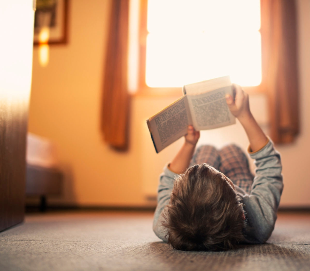 Little boy lying on the floor and reading a book. The boy is aged 6. Sunny day.
