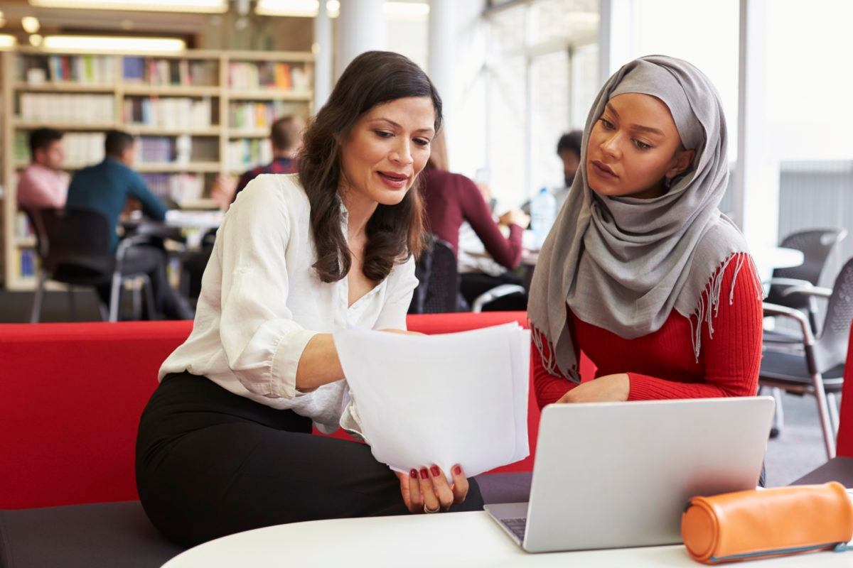 Female University Student Working In Library With Tutor