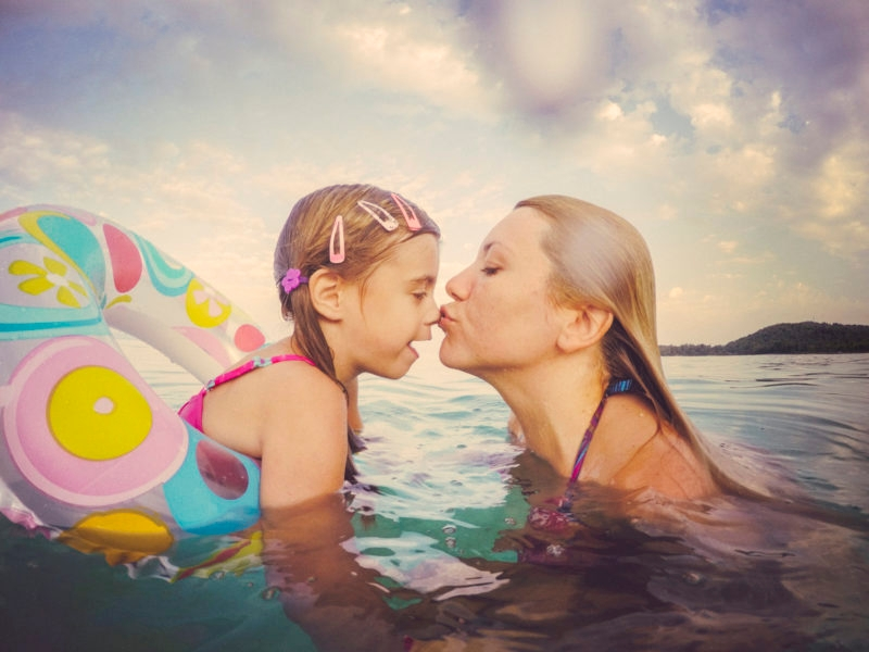 Mother and daughter are enjoying themselves in the sea. Real family, genuine emotions. Water splashes on the camera. Vintage toned.