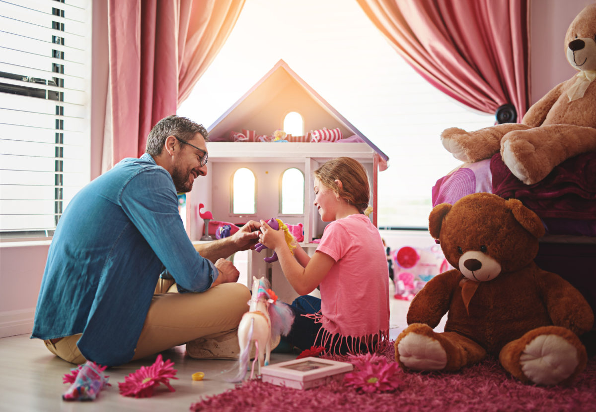 Shot of a father and daughter playing with a dollhouse together