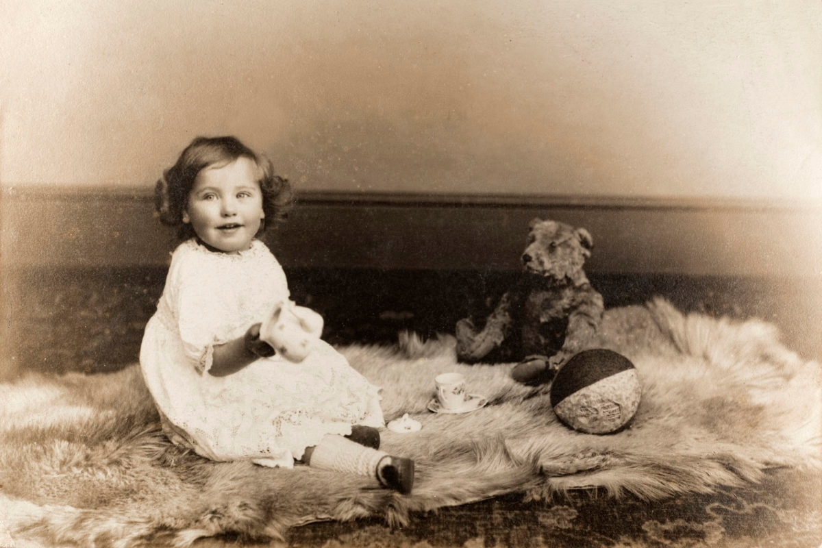 """Vintage black and white photograph of a baby girl sitting on an animal skin rug, with a teddy bear and toys, circa 1910. Some dust and scratches that reflect age of original image. See my vintage images lightbox, including similar baby boy shot..."""