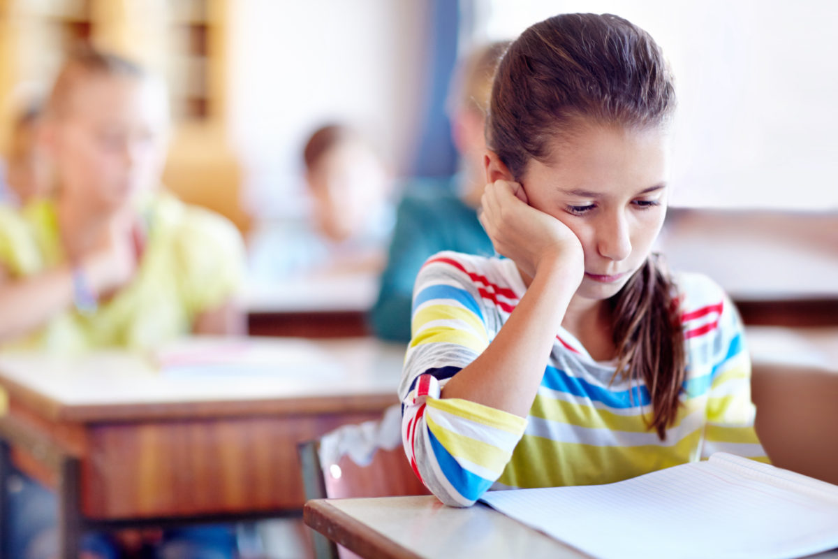 A young girl looking bored in class