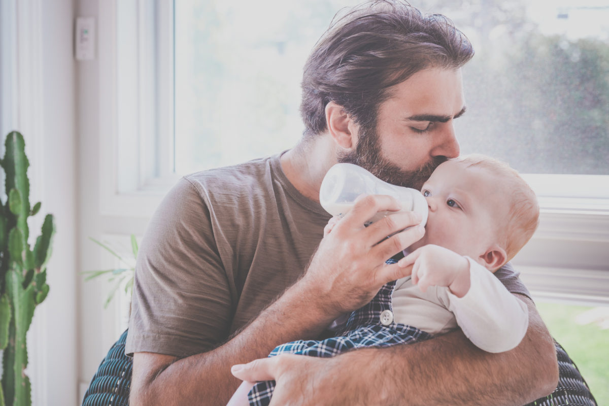 DSLR picture of a modern dad feeding his Baby boy with baby bottle inside sunroom.