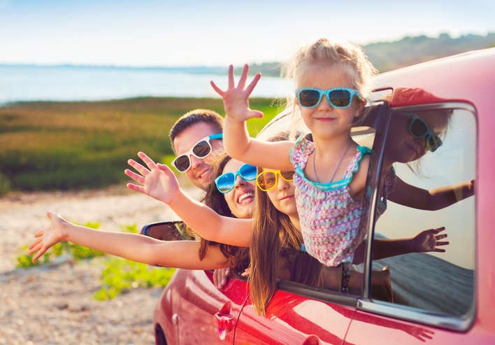 Portrait of smiling family with children at beach in car