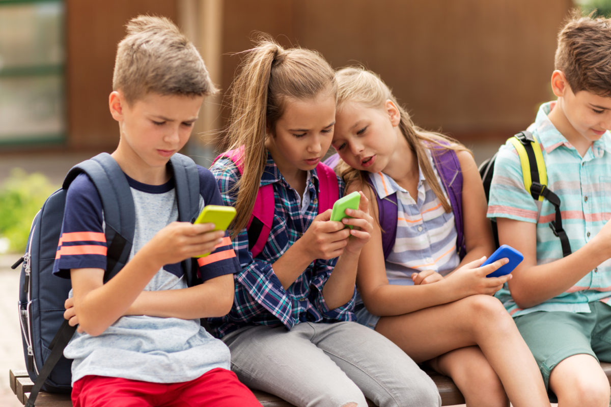 primary education, friendship, childhood, technology and people concept - group of happy elementary school students with smartphones and backpacks sitting on bench outdoors