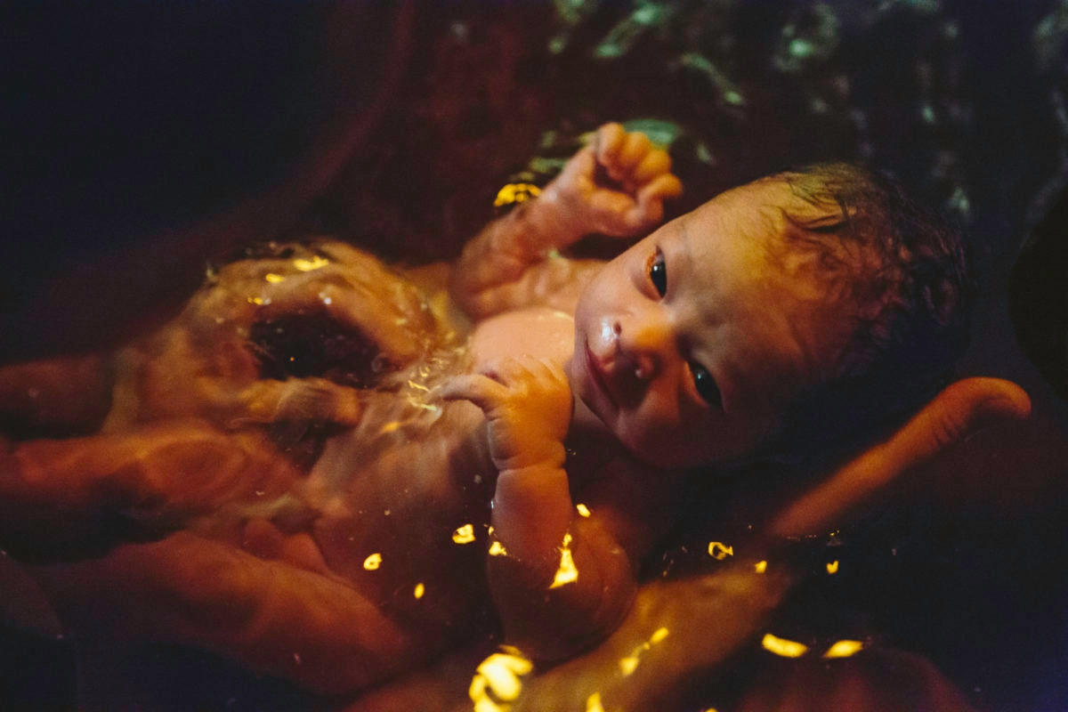 """A newborn baby, with umbilical cord still attached, soaks in the water of the birthing pool, eyes gazing up at it's mother. Lowlight, late night home birth with midwives."""