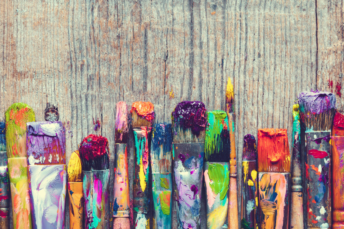 Row of artist paint brushes closeup on old wooden background.