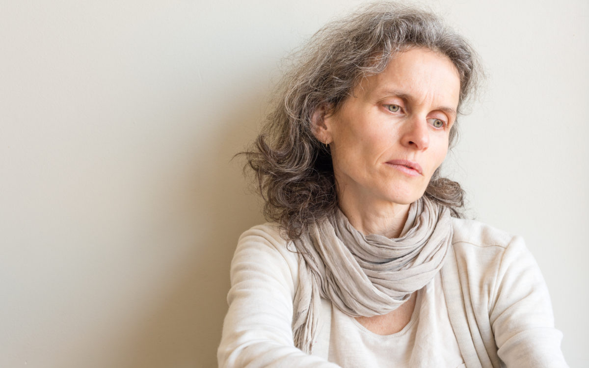 Middle aged woman with grey hair and cream clothing looking pensive against neutral wall
