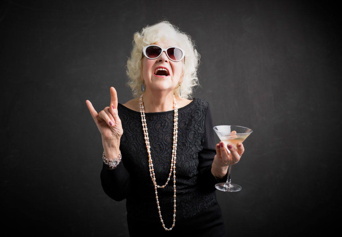 Cool grandmother with sunglasses and drink in hand showing rock sign