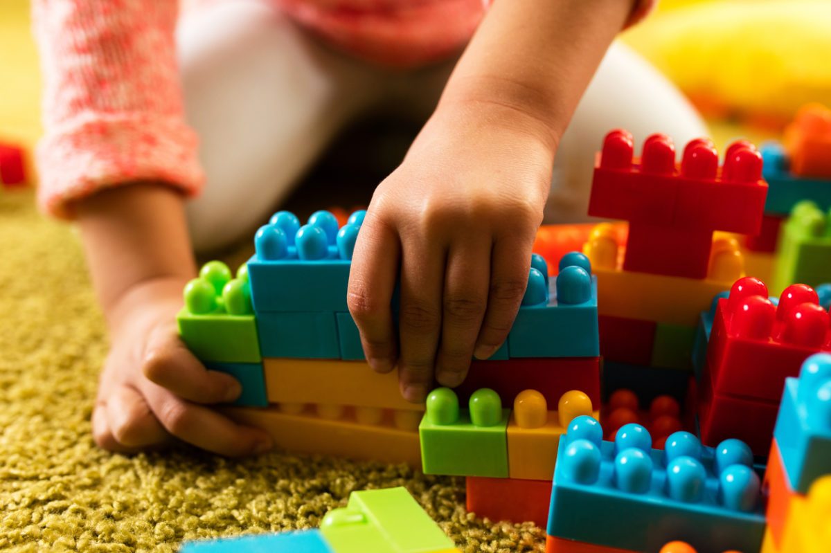 Close-up of child playing with toy blocks on the carpet.