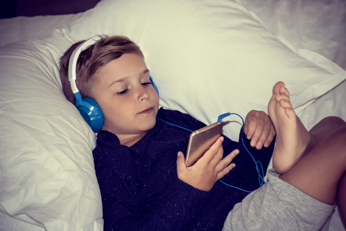 Small kid relaxing on the bed and listening music over headphones. Boy lying in bedroom and watching cartoons on mobile phone.