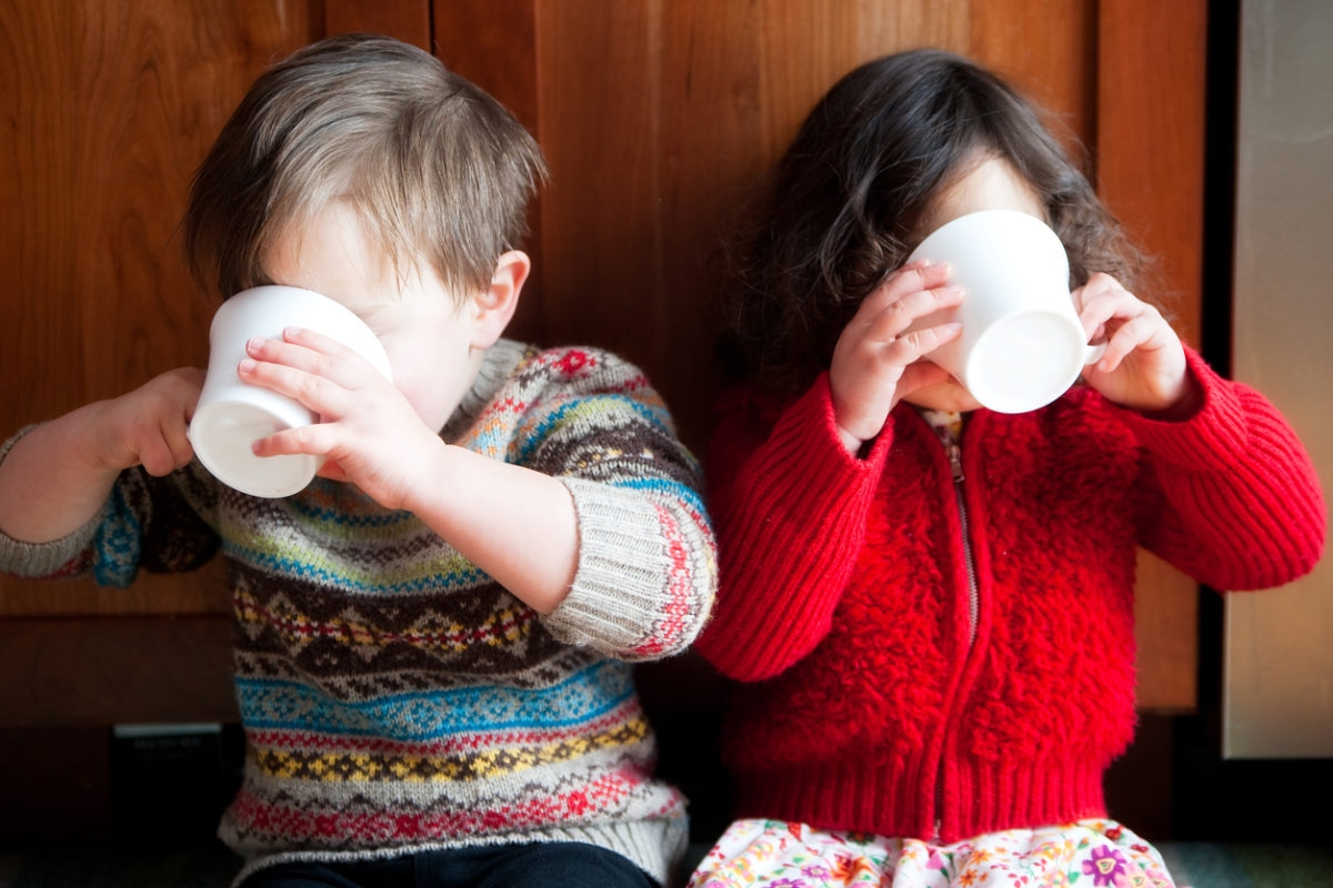Boy and girl, in cute sweaters, sipping from white mugs
