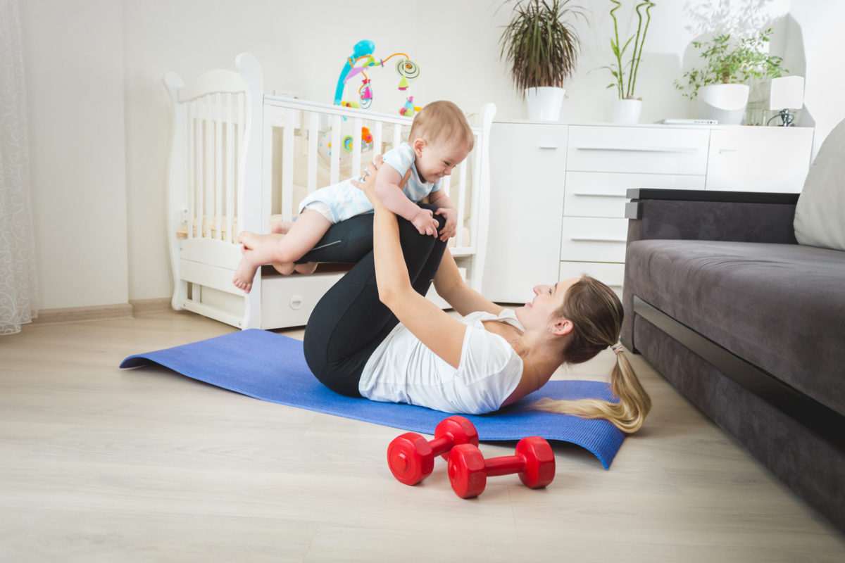 Beautiful mother holding baby and practicing yoga