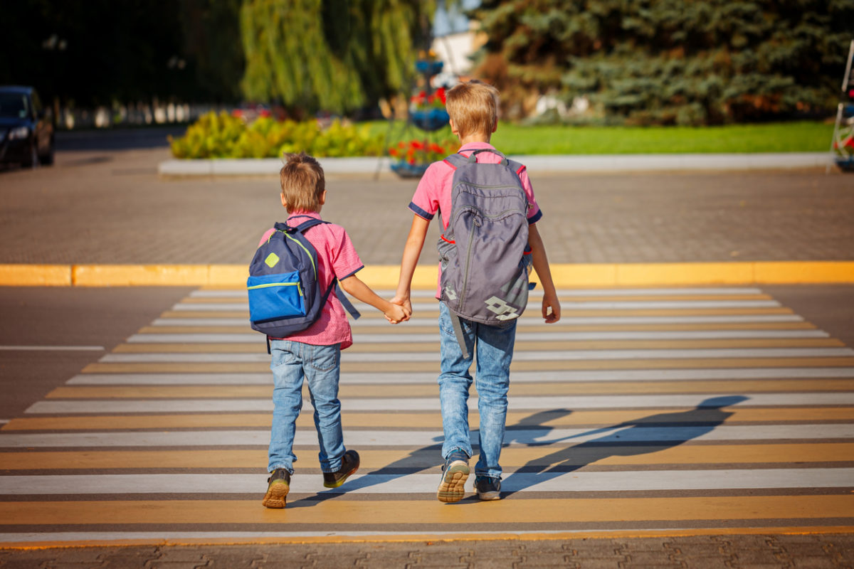 Two brothers, backpack walking, holding on warm day  on the