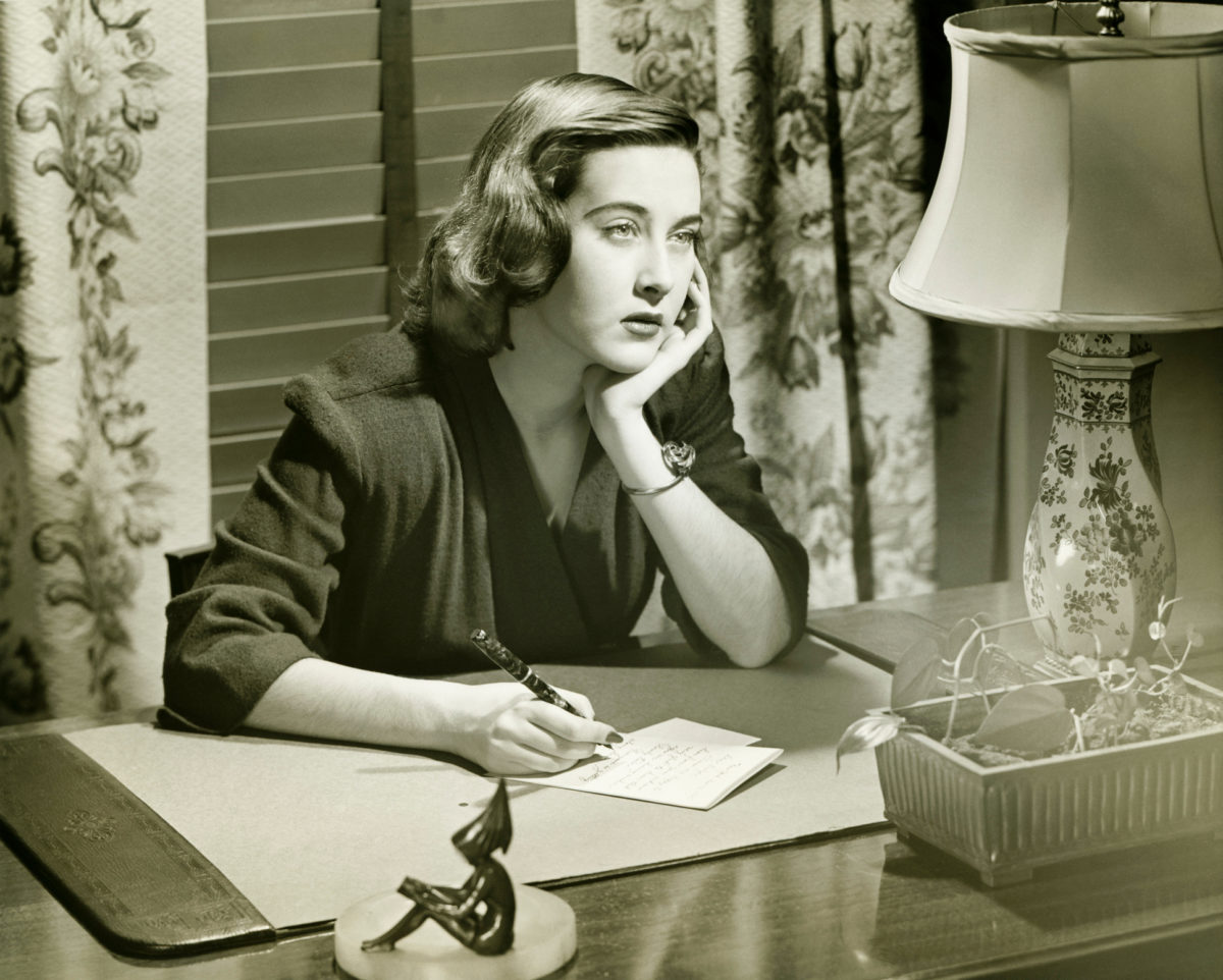 Thoughtful woman writing letter at desk, (B&W)