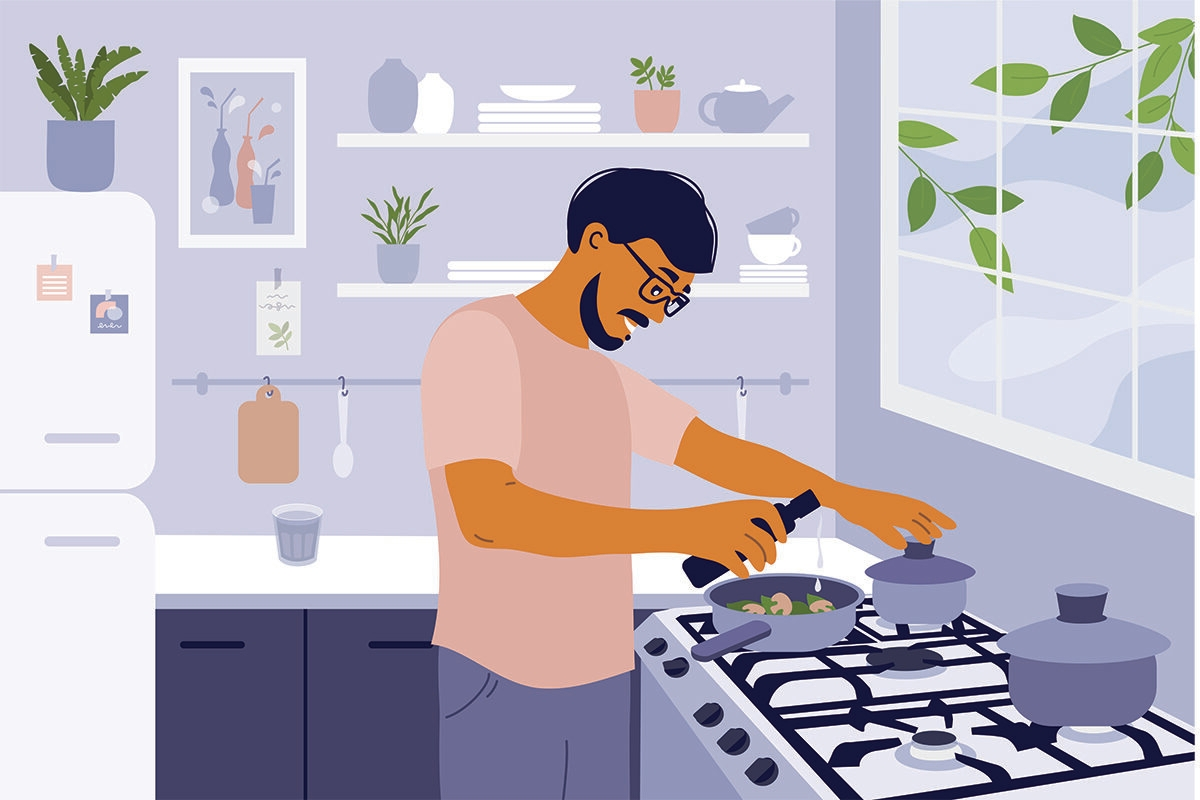 Smiling man cooking healthy meals in small cozy kitchen