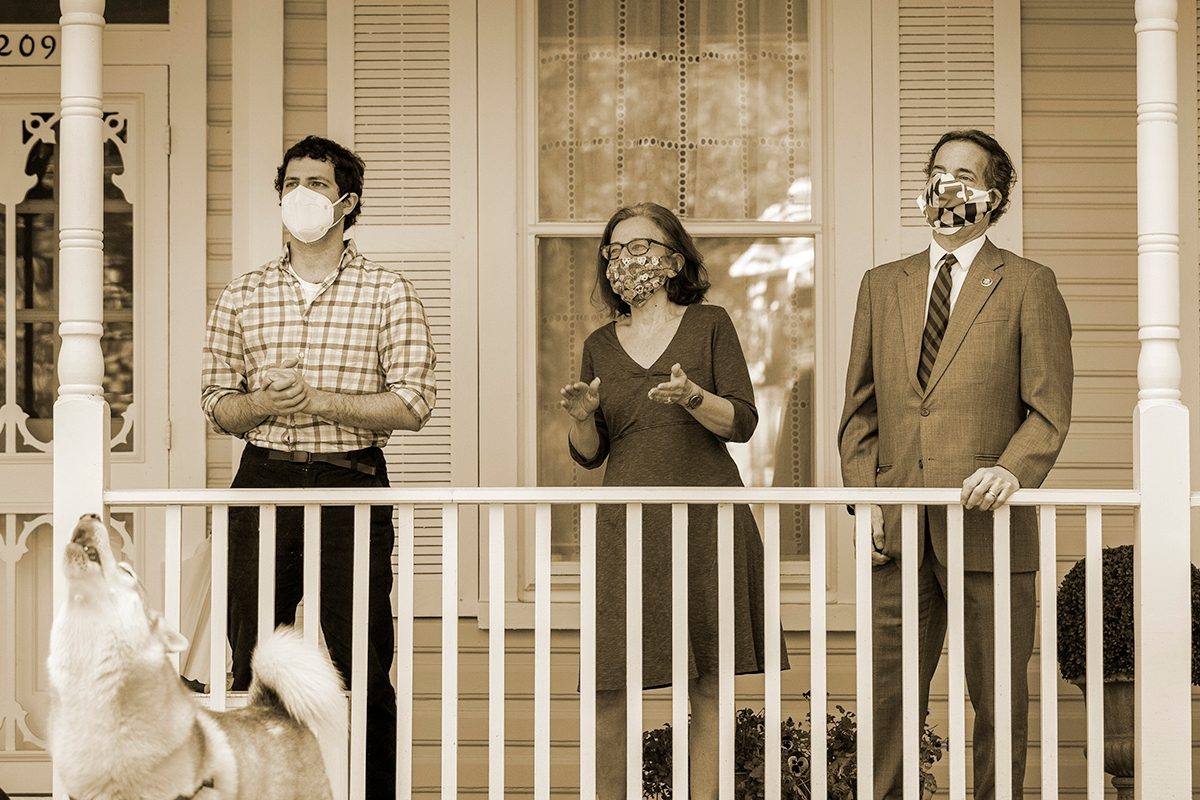 TAKOMA PARK, MD - MAY 04: (L-R) Thomas Raskin, Sarah Bloom Raskin and U.S. Rep. Jamie Raskin (D-MD) listen as a group of Maryland residents, calling themselves the 'Pandemic Comforters,' sing to them in the front yard of their home on May 4, 2020 in Takoma Park, Maryland. The singers wanted to use the nice weather to show gratitude to Rep. Raskinfor his work in Congress and offer their prayers during the coronavirus pandemic. Last week, Rep. Raskin was appointed by Speaker of the House Nancy Pelosi to the newly created House Select Committee On Coronavirus. (Photo by Drew Angerer/Getty Images)