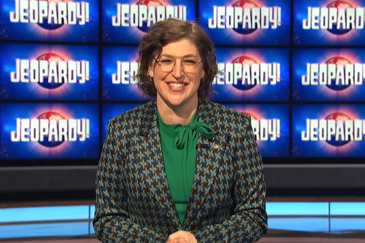 """Mayim Bialik in front of """"Jeopardy"""" background."""