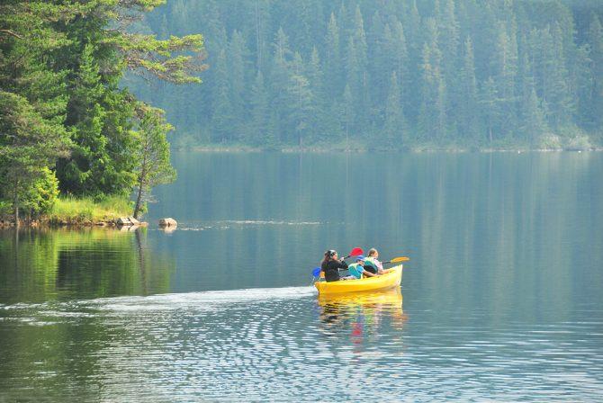 Kids kayaking on a lake.