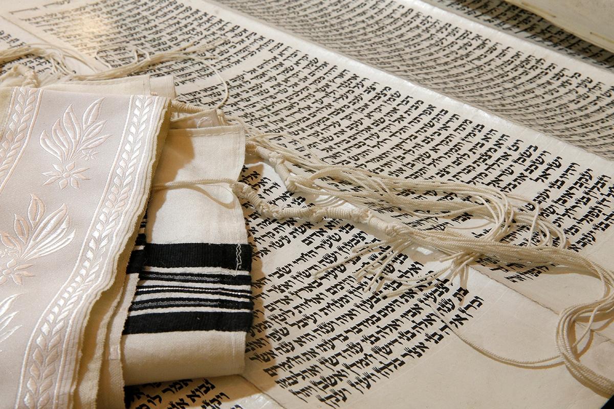 A Torah scroll and Jewish prayer shawl.