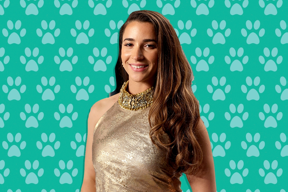 Aly Raisman in front of a paw print background