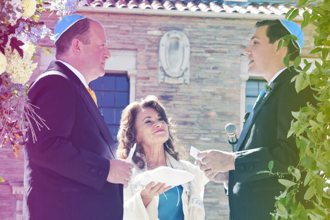 Jared Polis (L) marries partner Marlon Reiss (R) under a chuppah. Between them is officiating rabbi Tirzah Firestone
