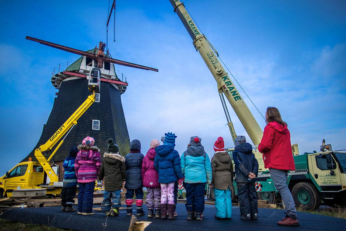 schoolchildren and teacher observe the lifting of a mill cap.