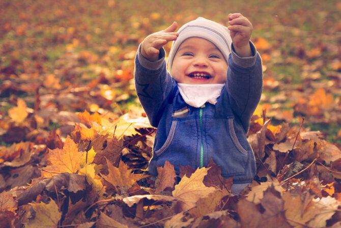happy baby playing in fall leaves