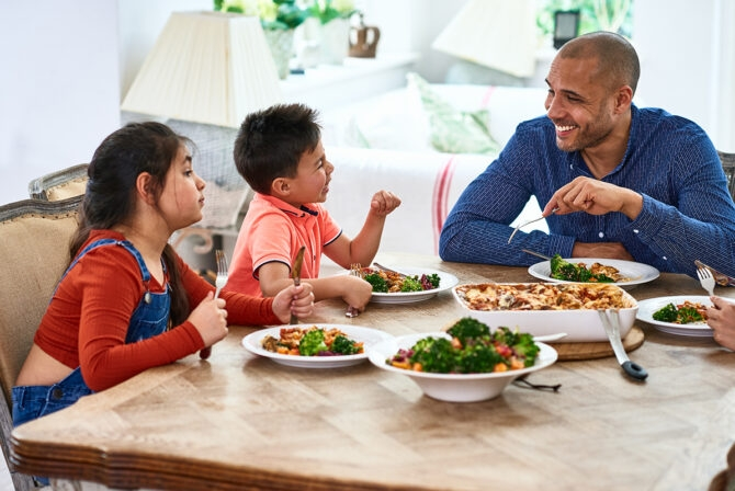 Cheerful father smiling and talking with family at meal time